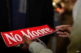 """Tori Sisson, right, receives a gift of chocolate and a """"No Moore,"""" sticker, named after Roy Moore,  from a supporter, near the Montgomery County Courthouse Sunday, Feb. 8, 2015."""
