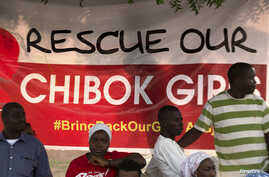 """Protesters from the remote town of Chibok stand next to a poster reading """"Rescue our Chibok girls,"""" at a protest calling for the release of abducted schoolgirls, in Abuja, Nigeria, May 16, 2014."""
