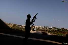 FILE - A Libyan rebel mans a check point on the outskirts of Benghazi, Libya, March 30, 2011. Fighting was continuing Saturday for control of the country's oil facilities around the city.