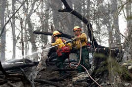 Firefighters Valarie Lopez, left, and Mark Tabaez work to cool hot spots after a wildfire burned a hillside in Clayton, Georgia, Nov. 15, 2016,