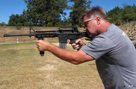 "Shooting instructor Frankie McRae aims an AR-15 rifle fitted with a ""bump stock"" at his 37 PSR Gun Club in Bunnlevel, North Carolina, Oct. 4, 2017."
