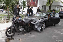Policemen examine a damaged Ferrari at the home of the late Red Bull founder Chaleo Yoovidhaya in Bangkok September 3, 2012.The grandson of the owner of Red Bull - the famous energy drink from Thailand - has been arrested for the hit and run death of