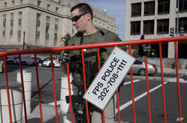 An armed U.S. Marshal lifts the security barricade around the federal courthouse in Washington Oct. 20, 2014, where Libyan militant Ahmed Abu Khattala's hearing was held.