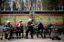 FILE - A group of elderly women rest in their wheelchairs at a residential compound in Beijing, China, March 31, 2016.