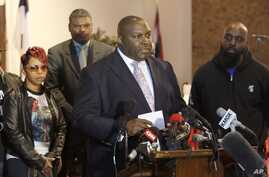 Attorney Daryl Parks, center, talks to reporters on behalf of Michael Brown's parents, Lesley McSpadden, left, and Michael Brown Sr., right, at a news conference in Dellwood, Mo., March 5, 2015.