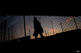 FILE - A migrant is seen walking after crossing a fence as he attempts to access the Channel Tunnel in Calais, northern France, Aug. 8, 2015.