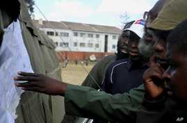 Voters look at posted results for Zimbabwe's national elections outside of a polling station in Harare, Aug. 1, 2013.