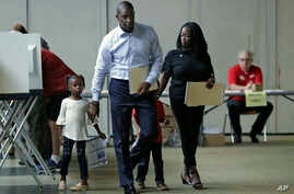 Florida Democratic gubernatorial candidate Andrew Gillum walks with his wife, R. Jai Gillum, and children Caroline and Jackson as he votes, Nov. 6, 2018, in Tallahassee, Fla. Gillum was running against Republican Ron DeSantis.