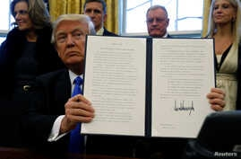 U.S. President Donald Trump holds an executive order dealing with members of the administration lobbying foreign governments, after signing it in the Oval Office at the White House in Washington, Jan. 28, 2017.