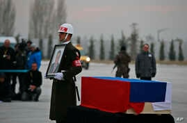 A Turkish forces honour guard stands by the Russia flag-draped coffin of Russian Ambassador to Turkey, Andrei Karlov, who was assassinated Monday, during a ceremony at the airport in Ankara, Turkey, Tuesday, Dec, 20, 2016.