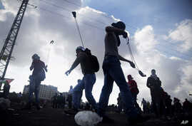 FILE - Palestinian protesters use slingshots to throw stones towards Israeli security forces during clashes following a protest marking the 11th anniversary of the death of late Palestinian leader Yasser Arafat, in the West Bank city of Ramallah, Wed