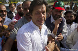 Imran Khan, cricketer-turned-politician and head of Pakistan Tehreek-e-Insaf (PTI) is surrounded with supporters as he leaves to lead a peace march against U.S. drone strikes from Islamabad to South Waziristan, October 6, 2012.