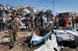 Somali soldiers walk through the wreckage after a car bomb that targeted a police station in the Waberi neighborhood, where President Hassan Sheikh Mohamud was visiting a university, in the capital Mogadishu, Somalia Saturday, Nov. 26, 2016.