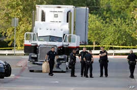 San Antonio police officers investigate the scene Sunday, July 23, 2017, where eight people were found dead in a tractor-trailer loaded with at least 30 others outside a Walmart store in stifling summer heat in what police are calling a horrific huma