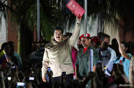 Venezuelan President Nicolas Maduro greets supporters after receiving a law which grants him with decree powers in Caracas, Nov. 19, 2013.