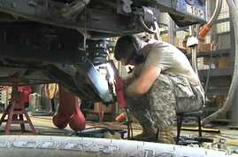 A National Guard soldier in Robbins, Illinois repairs a military Humvee