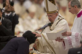 Pope Francis baptizes Rachel Khayesi of Kenya during an Easter vigil service in St. Peter's Basilica at the Vatican, April 4, 2015.