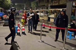 FILE - Residents walk past a security checkpoint at the close of a open-air market in Kashgar in western China's Xinjiang region, Nov. 4, 2017. Authorities are using detentions in political indoctrination centers and surveillance in efforts to contro
