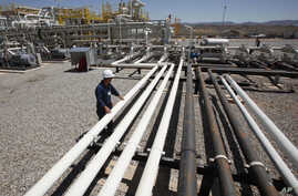 FILE - An employee works at the Tawke oil fields in the semiautonomous Kurdish region in northern Iraq, May 31, 2009.