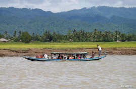 Rohingya people travel in a boat on a river in Buthidaung, Myanmar, Aug. 29, 2017. Three boats carrying Rohingya people fleeing violence in Myanmar for Bangladesh capsized Thursday.