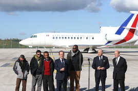 French president Francois Hollande (4thL) flanked by former French hostages and French Foreign Minister Laurent Fabius and Defense Minister Jean-Yves Le Drian upon the hostages' arrival at the military airport of Villacoublay outside Paris, Oct. 30,