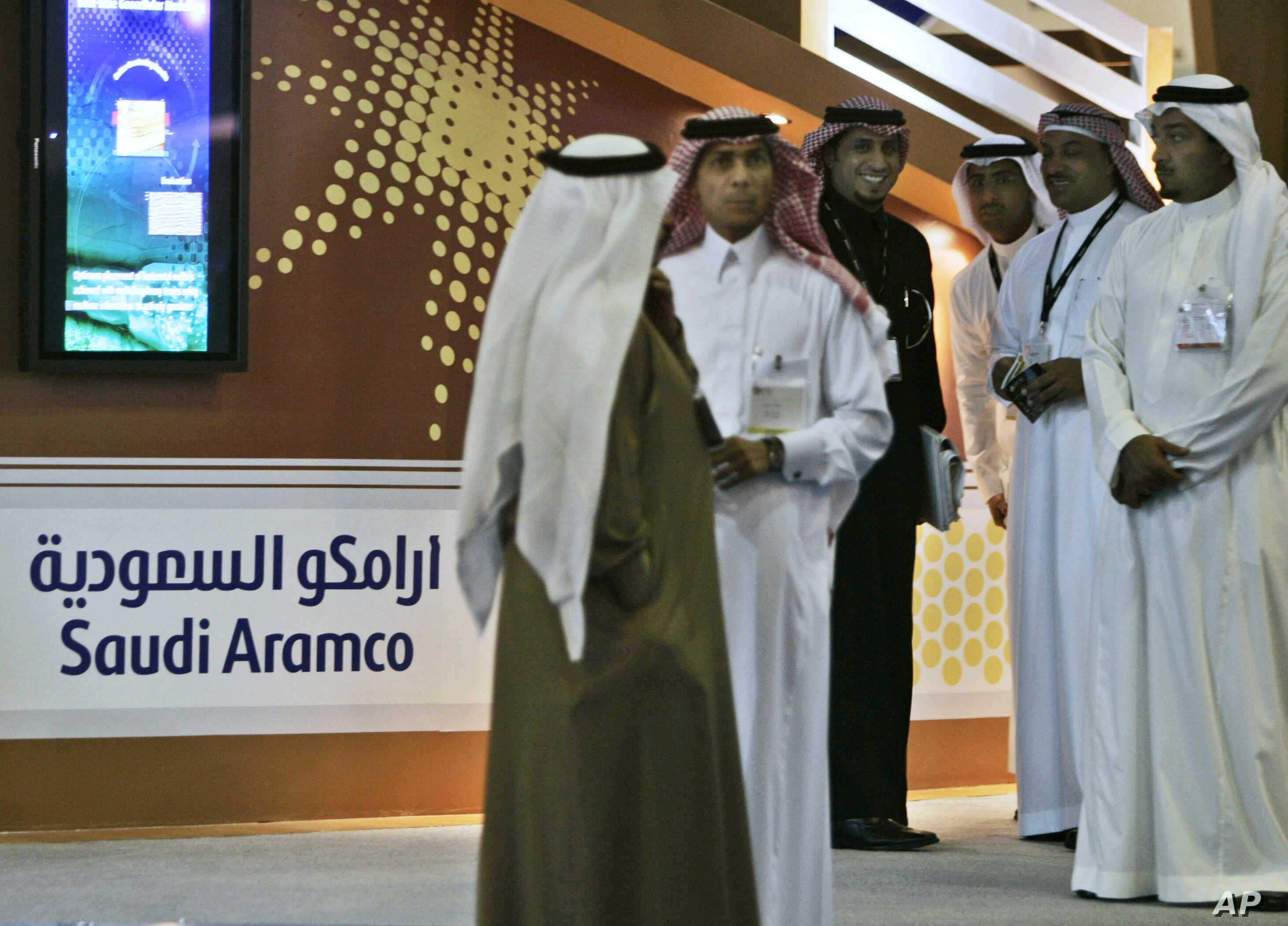 FILE - Employees of the Saudi Aramco oil company prepare for the first day of the Arab Oil and Gas exhibition in Dubai, United Arab Emirates.