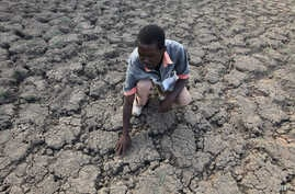 Zimbabwe Drought: Last Zimaniwa feels the broken ground at a spot which is usually a reliable water source that has dried up due to lack of rains in the village of Chivi , Zimbabwe, Jan. 29, 2016.