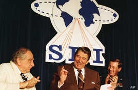 "FILE - U.S. President Ronald Reagan is flanked by physicist Dr. Edward Teller, left, and Lt. Gen. James A. Abrahamson, director of Strategic Defense Initiative, as he arrives to address a conference marking the first five years of his ""Star Wars"" mis"