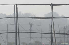 FILE - A laborer dismantles scaffolding near the India Gate war memorial on a smoggy day in New Delhi.