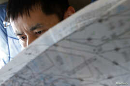 A Japan Coast Guard officer studies a map onboard their Gulfstream V Jet aircraft, customized for search and rescue operations, as they search for the missing Malaysia Airlines MH370 plane over the waters of the South China Sea, March 15, 2014.