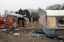 Workers dismantle migrants' dwellings in a makeshift camp near Calais, France, March 1, 2016. The slow tear-down of the encampment in Calais continued Tuesday, angering migrants who live there in squalid conditions in hopes of reaching a better life