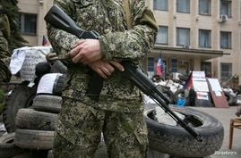 A pro-Russian armed man stands guard outside a regional government building seized by them in Kramatorsk, eastern Ukraine, April 22, 2014.
