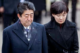 FILE - Japanese Prime Minister Shinzo Abe, left, and his wife Akie Abe take part in a wreath laying ceremony at the Antakalnis Memorial Cemetery in Vilnius, Lithuania, Jan. 14, 2018.