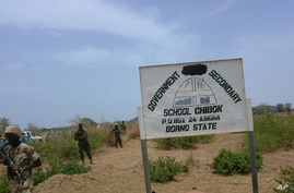 In this photo taken April, 21. 2014, soldiers stand guard in front of  government secondary school Chibok, were gunmen abducted more than 200 students in Chibok, Nigeria.