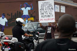 FILE - A demonstrator holding a placard blocks the path of a Los Angeles Police Department officer during a rally against the Missouri grand jury's decision in the Michael Brown case and the LAPD's fatal shooting in August of Ezell Ford, in Los Angel