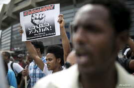 FILE - An Eritrean refugee holds a placard during a protest against the Eritrean government outside their embassy in Tel Aviv, Israel May 11, 2015.