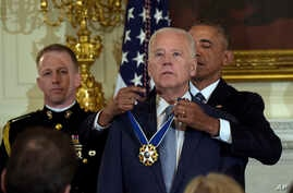 President Barack Obama presents Vice President Joe Biden with the Presidential Medal of Freedom during a ceremony in the State Dining Room of the White House in Washington, Jan. 12, 2017.