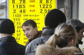People walk past a currency exchange office in Kyiv Feb. 5, 2014.