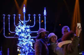 People take pictures in front of a Menorah during the Jewish festival of Hannukah, in Istanbul, Dec, 24, 2016