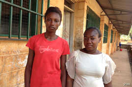 Elizabeth Issa ( left) stands with a fellow student outside a school offering classes for pregnant and lactating mothers in Freetown , Sierra Leone, Feb. 22, 2016. (Photo: Nina deVries for VOA)