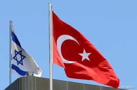 FILE - A Turkish flag flutters atop the Turkish embassy as an Israeli flag is seen nearby, in Tel Aviv, Israel, June 26, 2016.