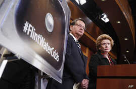 FILE - Sen. Gary Peters, D-Mich., left, and Sen. Debbie Stabenow, D-Mich., listen to a question as they discuss proposed legislation to help Flint, Michigan, with its current water crisis during a news conference on Capitol Hill in Washington, Jan. 2...