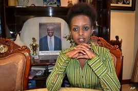 In this photo taken May 14, 2017, women's rights activist and presidential candidate Diane Shima Rwigara, 35, is photographed next to a portrait of her father, business tycoon Assinapol Rwigara, at her home in Kigali, Rwanda.