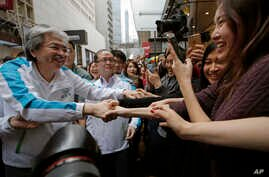 Chief Executive candidate, Hong Kong's former Financial Secretary John Tsang, left, shakes hands with his supporters at an election campaign in Hong Kong, March 24, 2017.