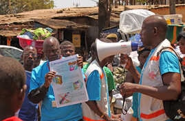 FILE - Health workers teach people about the Ebola virus and how to prevent infection,  in Conakry, Guinea.