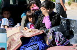 FILE - Civilians, allegedly wounded by Islamic State fighters, wait with relatives to cross into Turkey at the Syrian-Turkish border crossing of Tel Abyad, Syria, June 25, 2015.