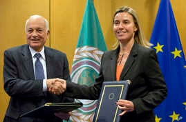 Secretary General of the Arab League Nabil Al-Araby, left, shakes hands with European Union High Representative Federica Mogherini after signing a cooperation agreement following a meeting of EU foreign ministers in Brussels, Jan. 19, 2015.