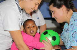 Laura Grobicki (left) and Stephanie Benn give therapy to a patient with cerebral palsy at Zithulele Hospital in South Africa ( Photo D.Taylor)