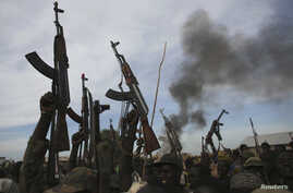 Rebel fighters hold up their rifles as they walk in front of a bushfire in a rebel controlled territory in Upper Nile State, South Sudan, Feb. 13, 2014.