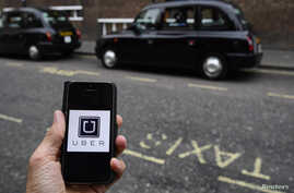 FILE - A photo illustration shows the Uber app logo displayed on a mobile telephone, as it is held up for a posed photograph in central London, Britain October 28, 2016.